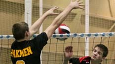 A volleyball player blocking a ball over the net