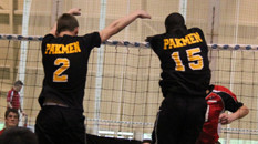 Two volleyball players doing a double block