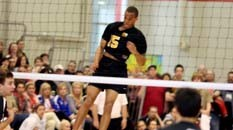 A volleyball player standing behind a net