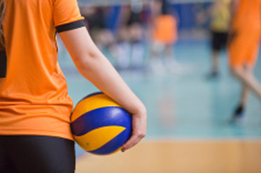 A girls hand on a volleyball