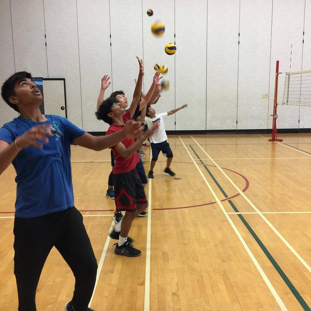 Boys volleyball players practicing to hit a ball